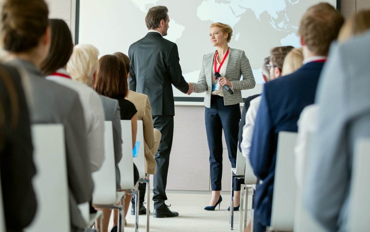 Business people shaking hands during seminar at convention | How To Identify and Capture Market Trends For Your Business