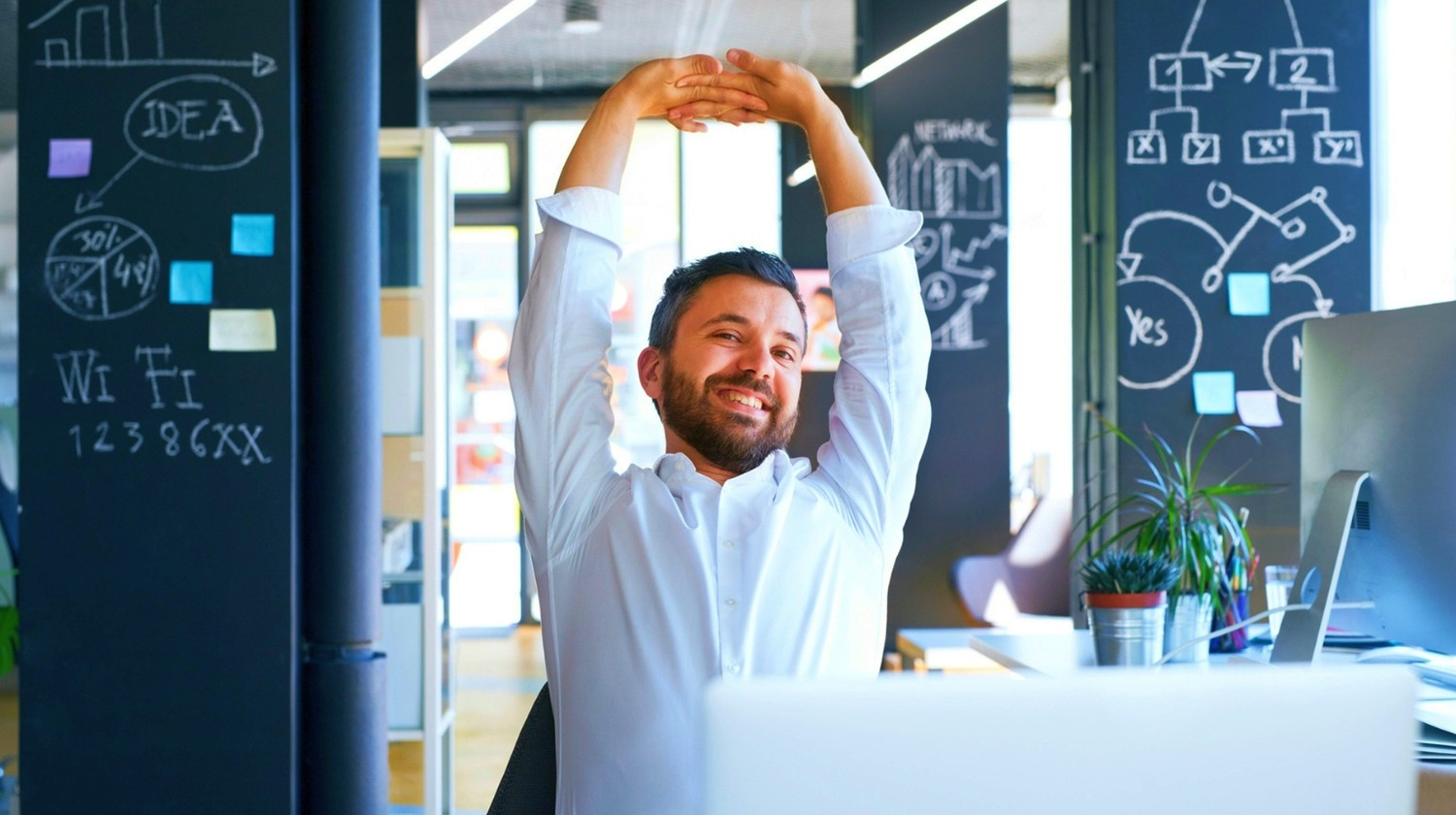 Featured | Businessman at the desk in his office stretching arms | How To Stay Productive In A World Full Of Distractions