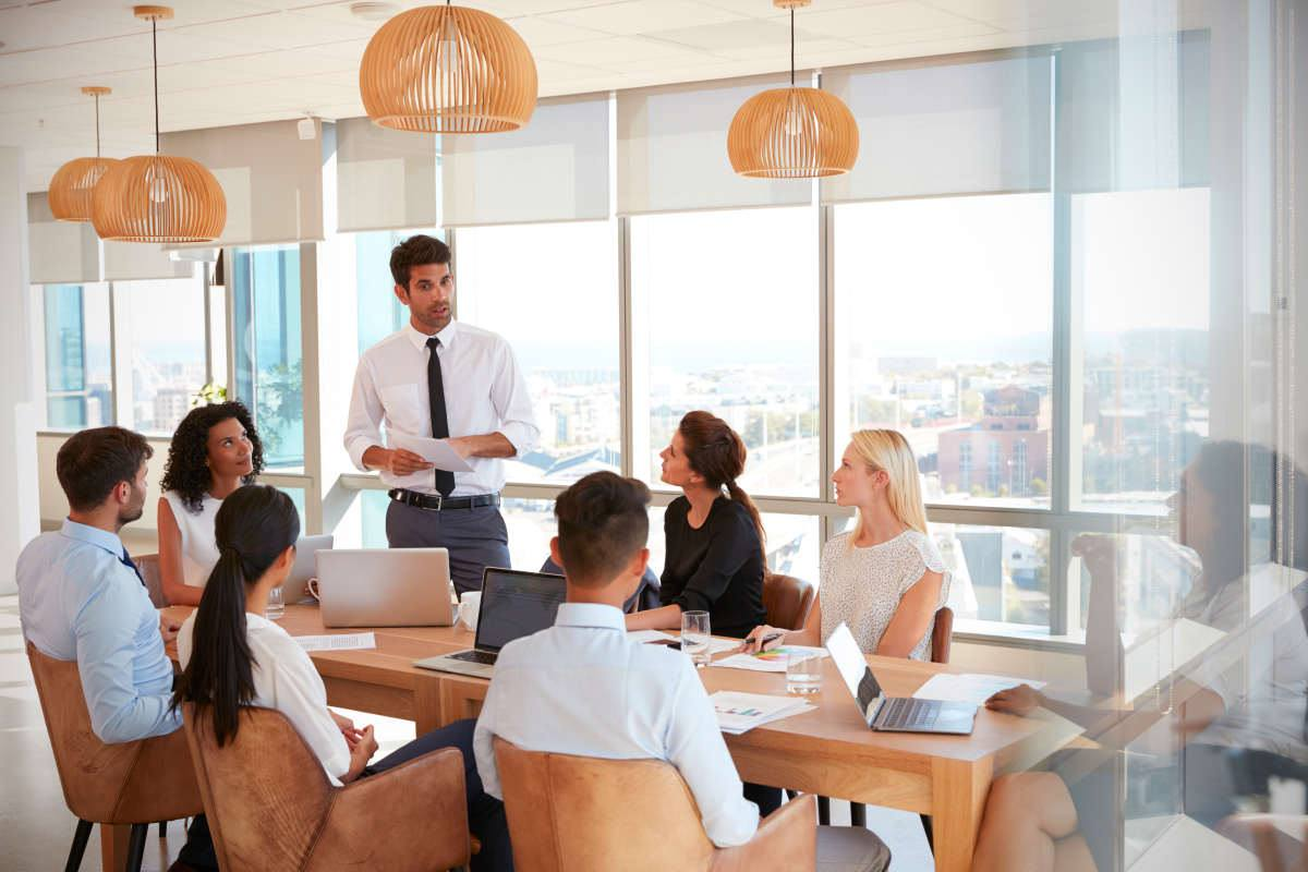 Businessman Leads Meeting Around Table Shot Through Door | Guilt-Free Ways To Say No (In Business Or Relationships)
