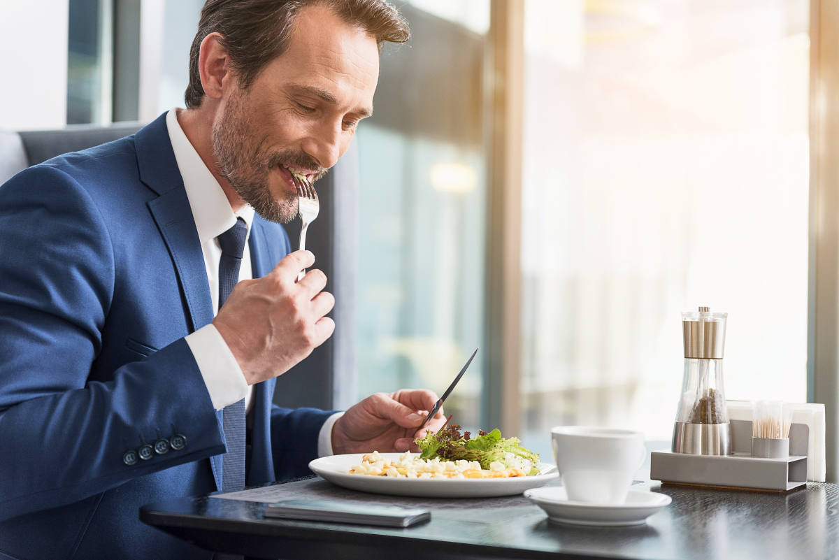 Cheerful businessman eating food in restaurant | How To Improve Yourself Every Day