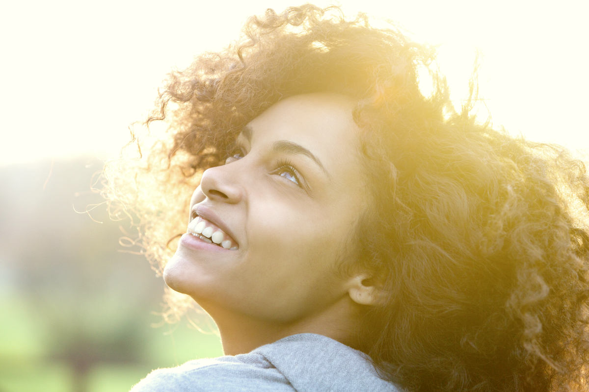 Beautiful young african american woman smiling and looking up | Life Lessons You'd Tell Your Younger Self | when we are young