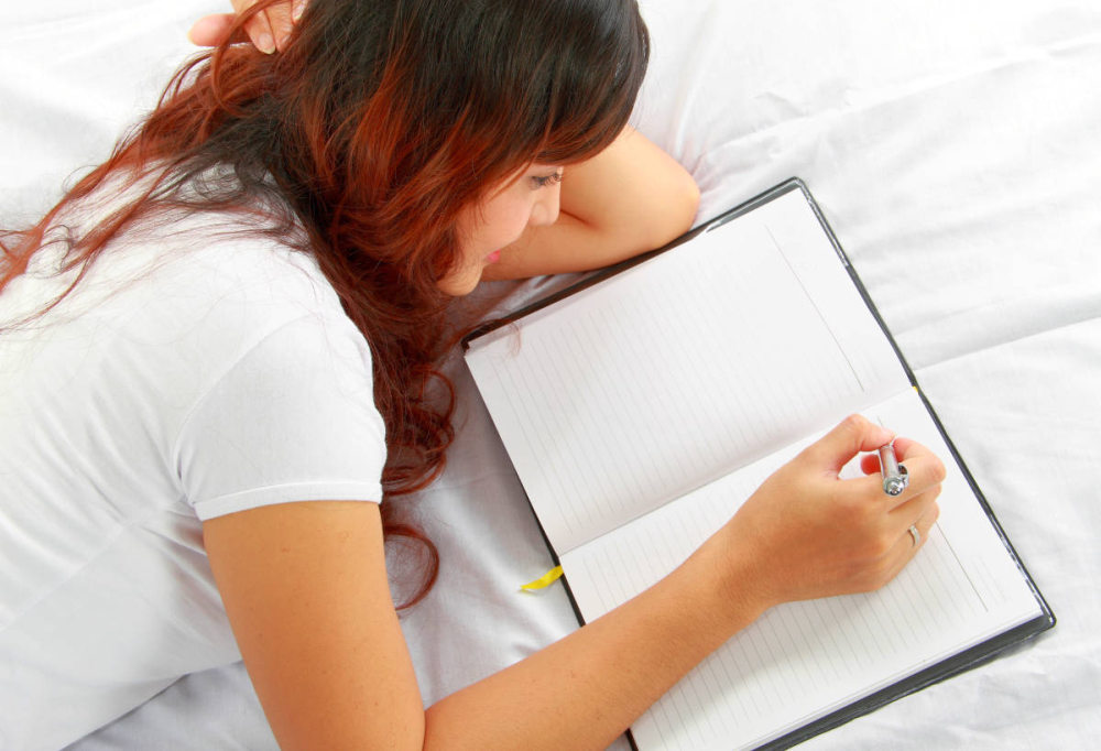 Relaxed young girl writing book while lying on the bed | How To Stop Being Pessimistic and Start Thinking Positive | positive psychology