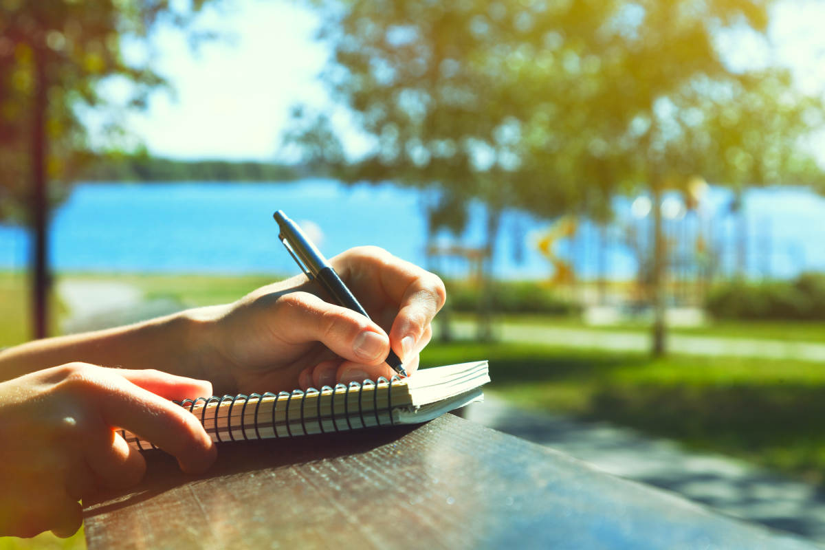 Girls hands with pen writing on notebook in park | Simple Rules To Finding Happiness In Life