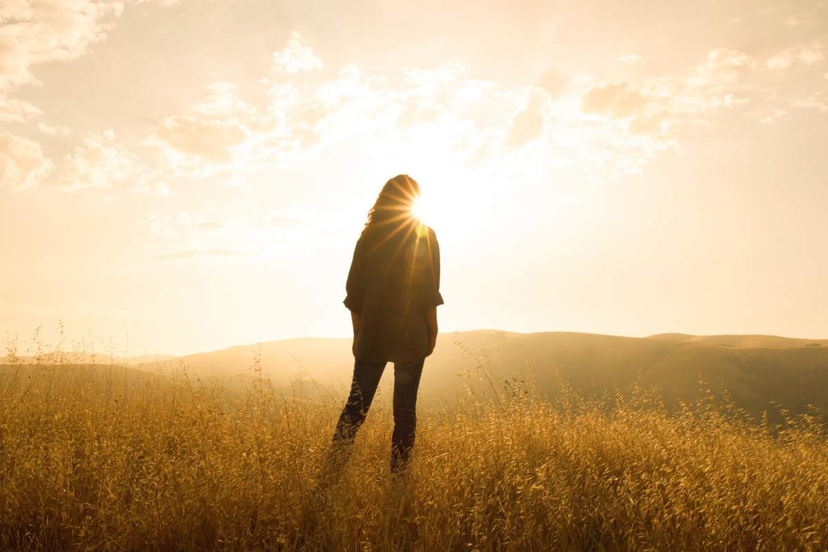 Woman standing in a field | Ways To Live Your Life With Purpose