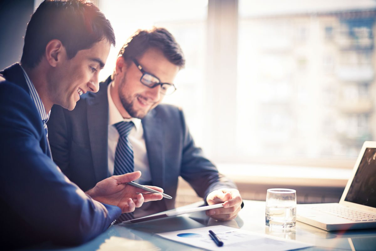 Image of two young businessmen using touchpad at meeting | Guilt-Free Ways To Say No (In Business Or Relationships)