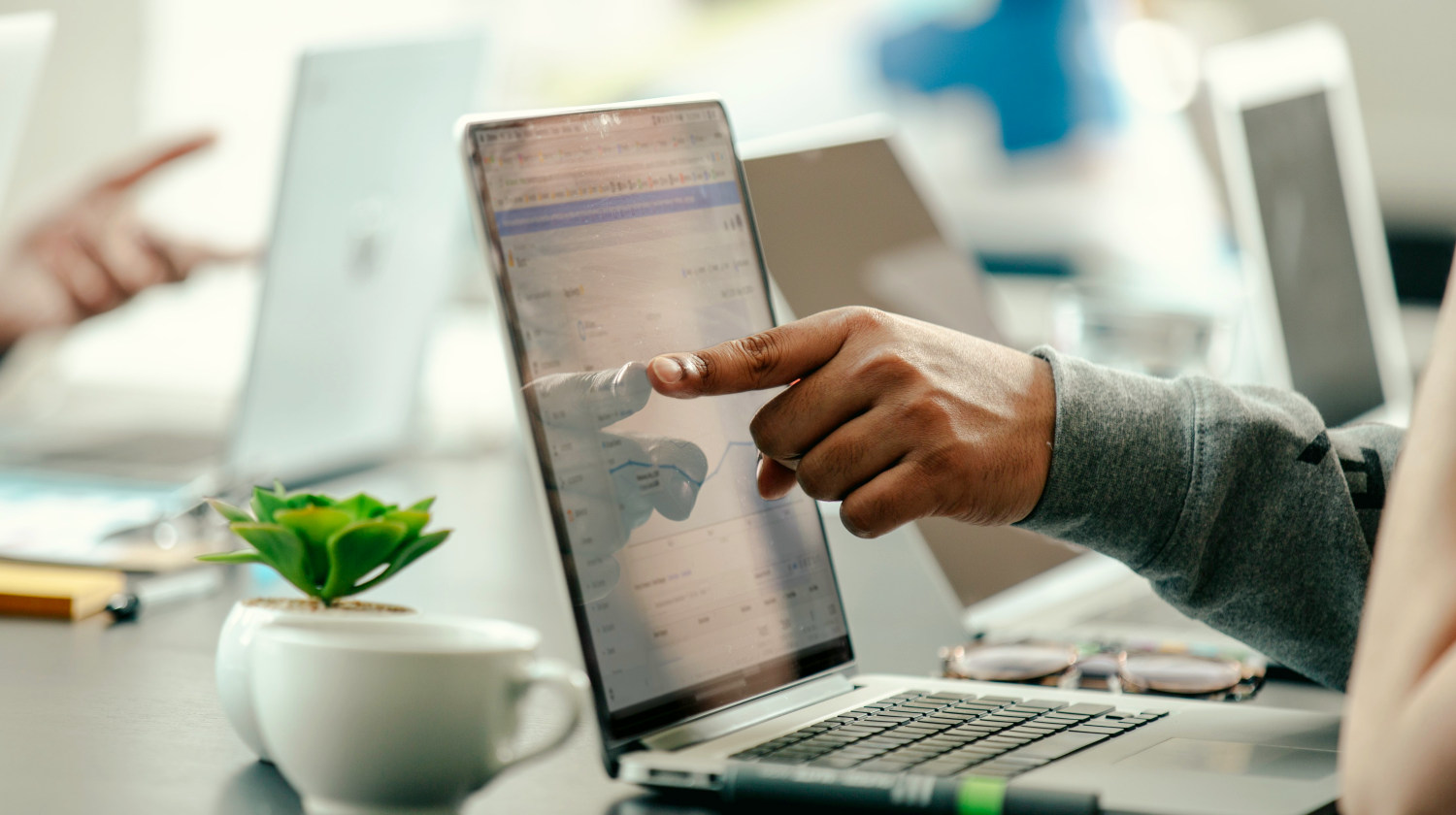 Featured | Man pointing at laptop screen analytics | How To Identify and Capture Market Trends For Your Business