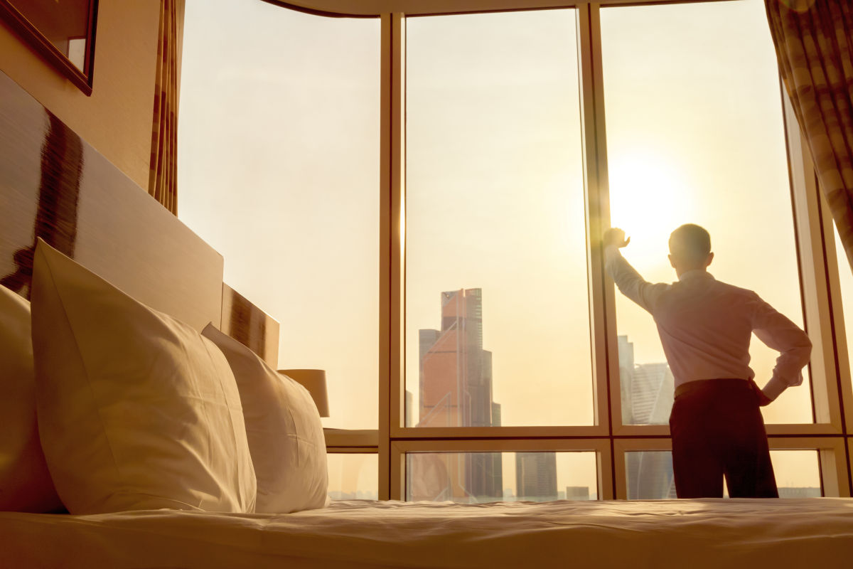 Young businessman standing at window in confident pose | How To Improve Yourself Every Day