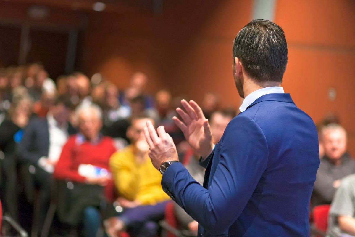 Public speaker giving talk at Business Event | Tips To Gain Confidence In Public Speaking