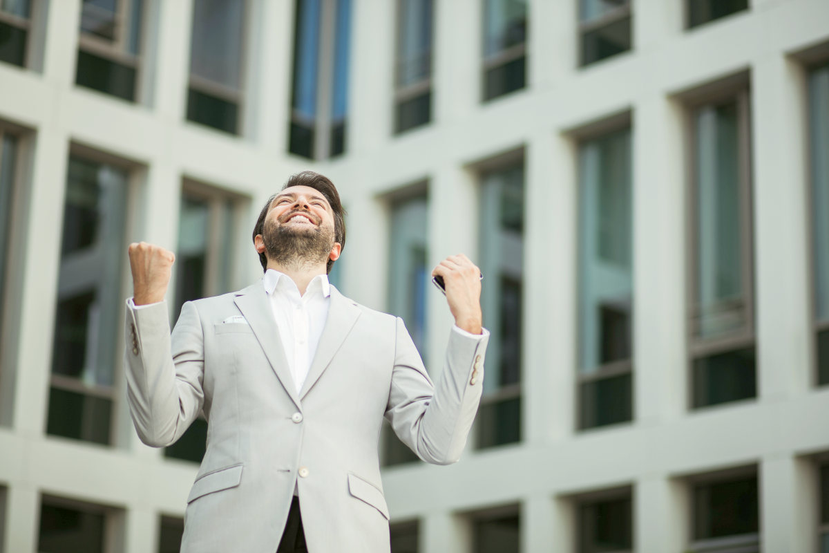 Successful businessman very excited in front of an office building | Life Lessons You'd Tell Your Younger Self | i wish i knew then what i know now