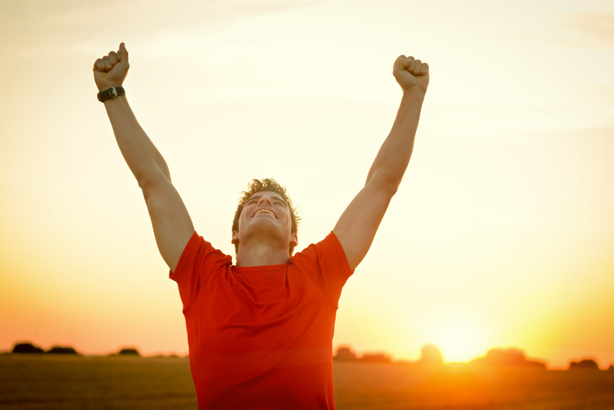 Successful man raising arms after cross track running on summer sunset | How to Reinvent Yourself and Improve Your Well-being