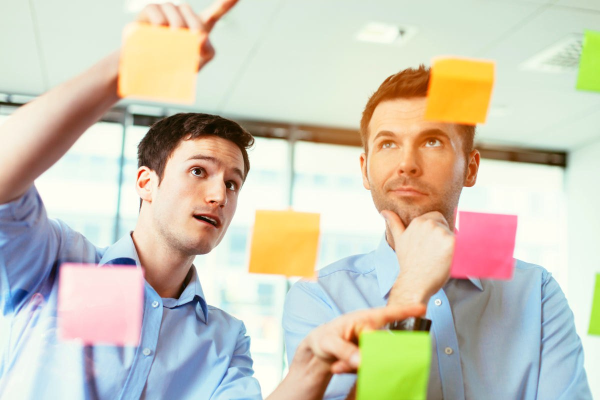 Two businessmen discussing ideas written on sticky notes | How To Handle Rejection As An Entrepreneur