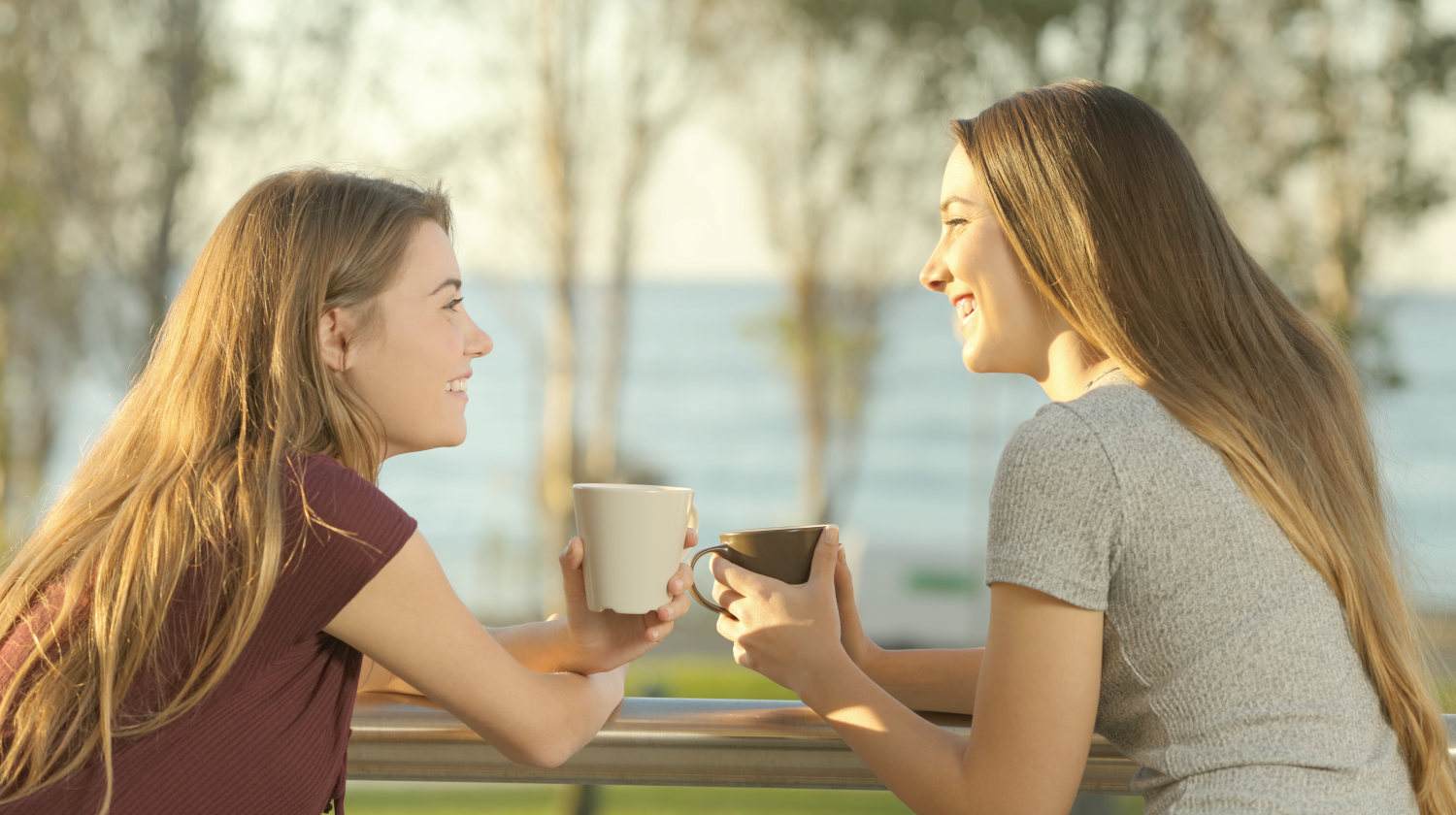 Two happy friends talking outdoors in an apartment balcony in the beach | Life Lessons You'd Tell Your Younger Self | Featured | life lesson quotes