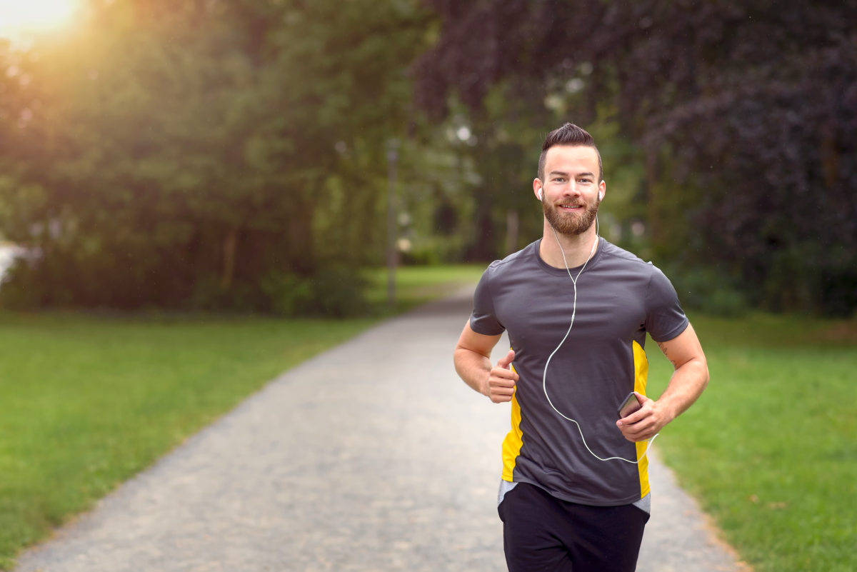Fit bearded young man jogging through a park listening to music | Ways To Set Yourself Free | how to live freely