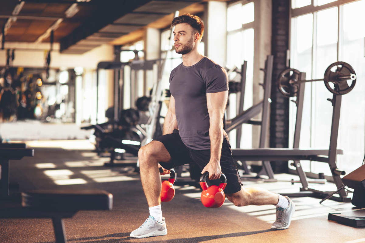 """Handsome man legs workout with kettlebell in the gym 