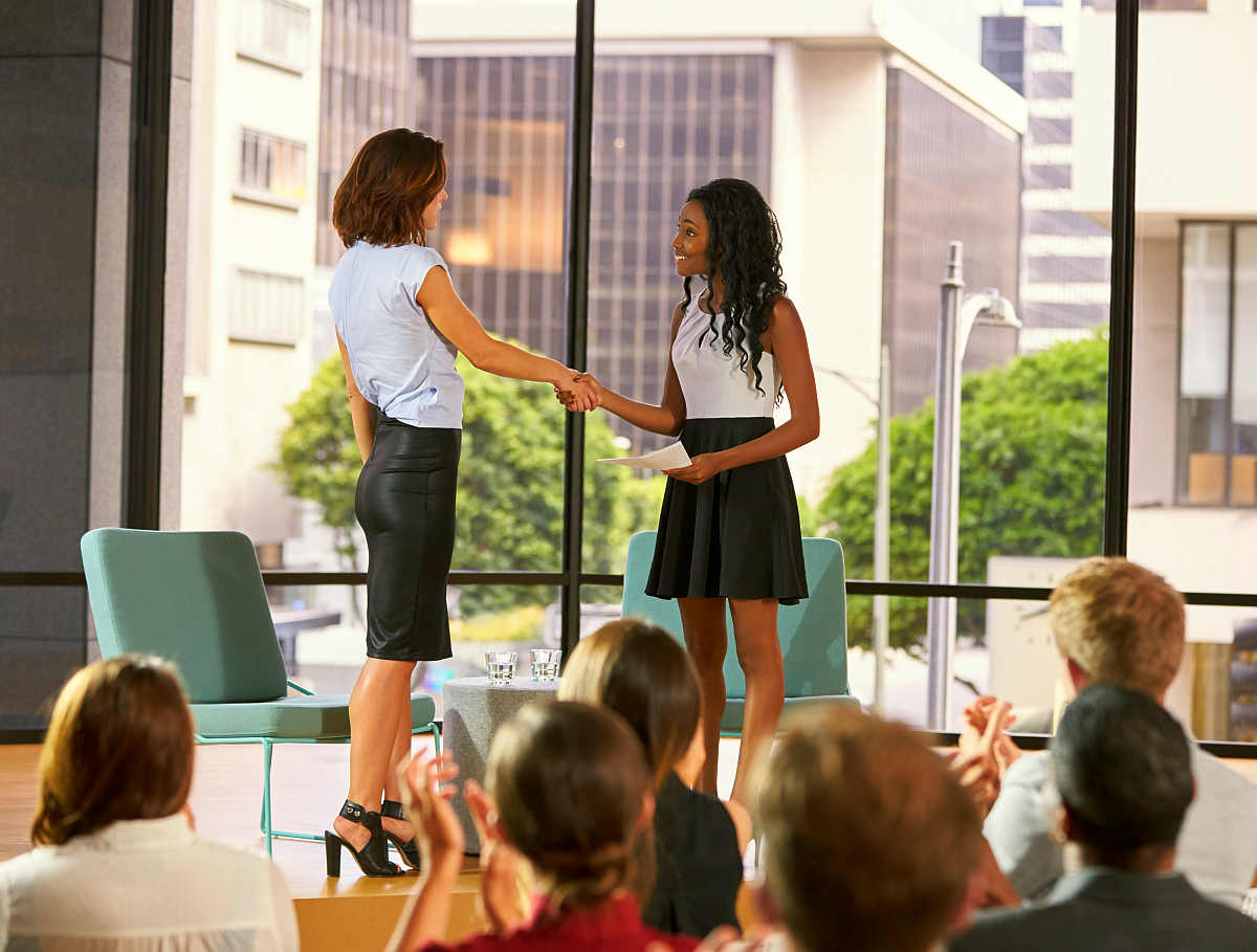 Interviewer greeting speaker on stage at a business seminar | Ways To Make A Positive Impact on Other People | big impact