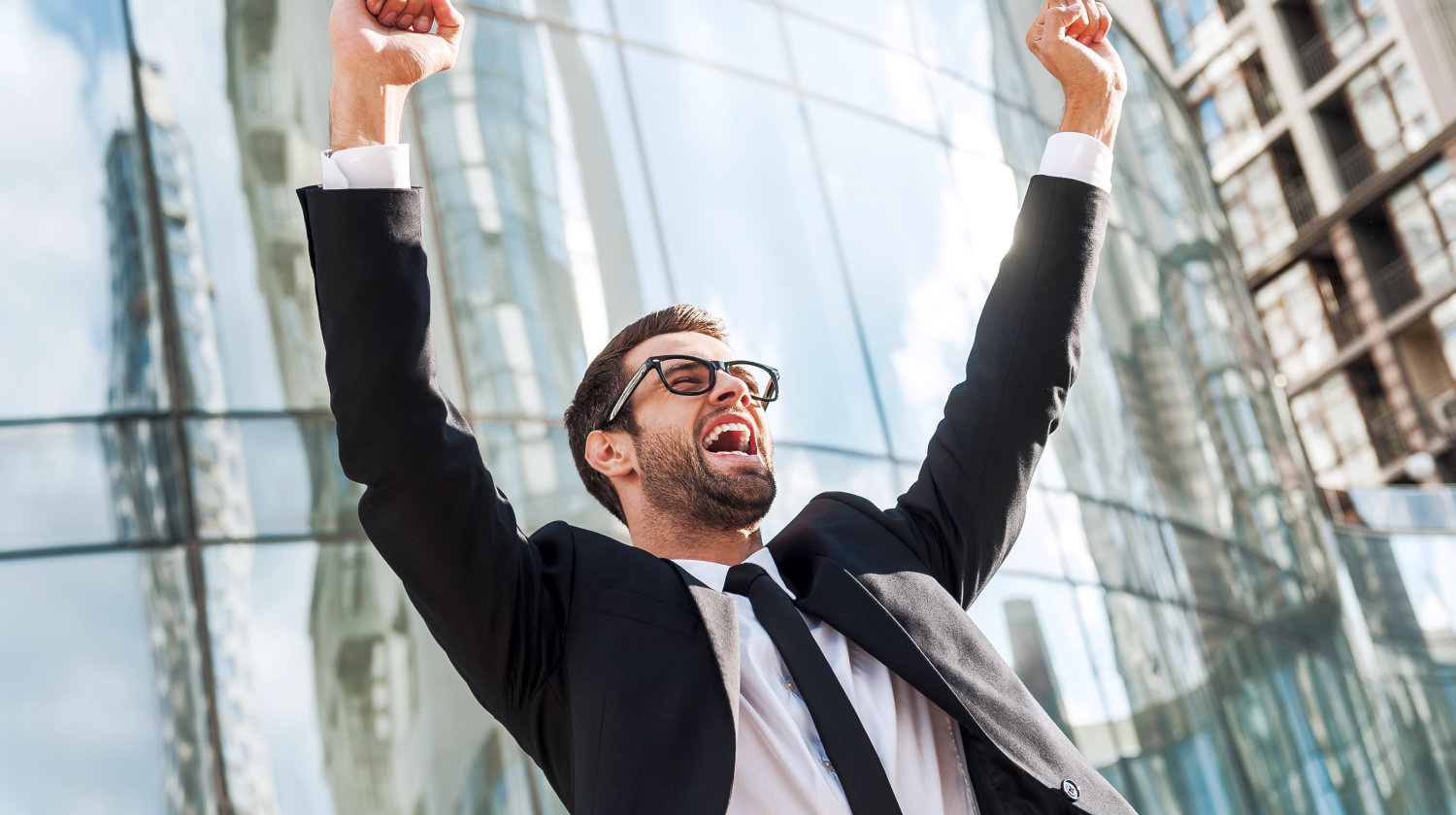 """Excited young businessman keeping arms raised 