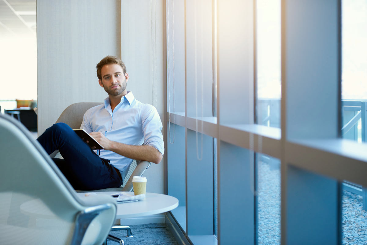 """Positive young businessman sitting in a modern corporate environment 
