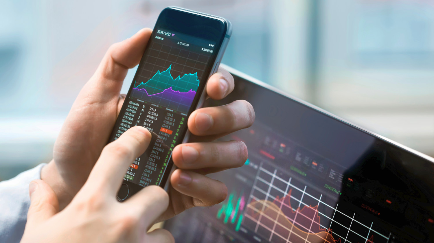 Business man holding phone | Investing 101: A Beginner's Guide To Investing | investing in stocks | Featured