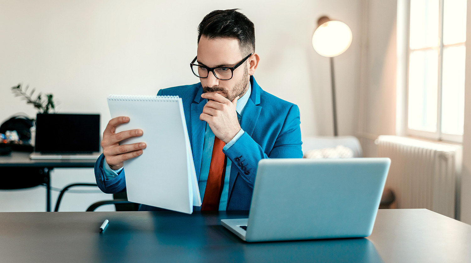 Young businessman reading documents at office desk | Mini Habits You Can Do In 20 Minutes To Be One Percent Better | productivity habits | Featured