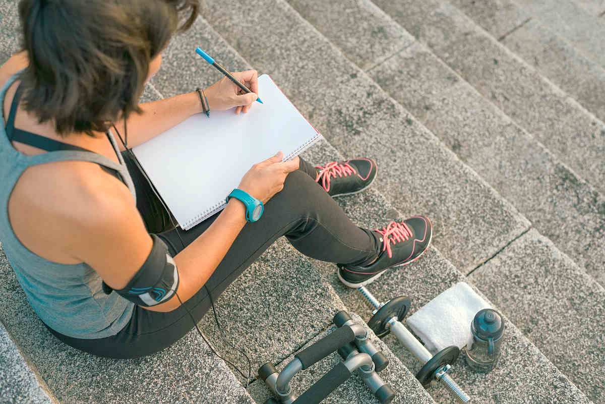Fitness sporty woman writing on blank notepad while sitting on urban stone stairs | Reasons Why Self-Empowerment Is Important | How You Can Empower Yourself | self empowerment quote