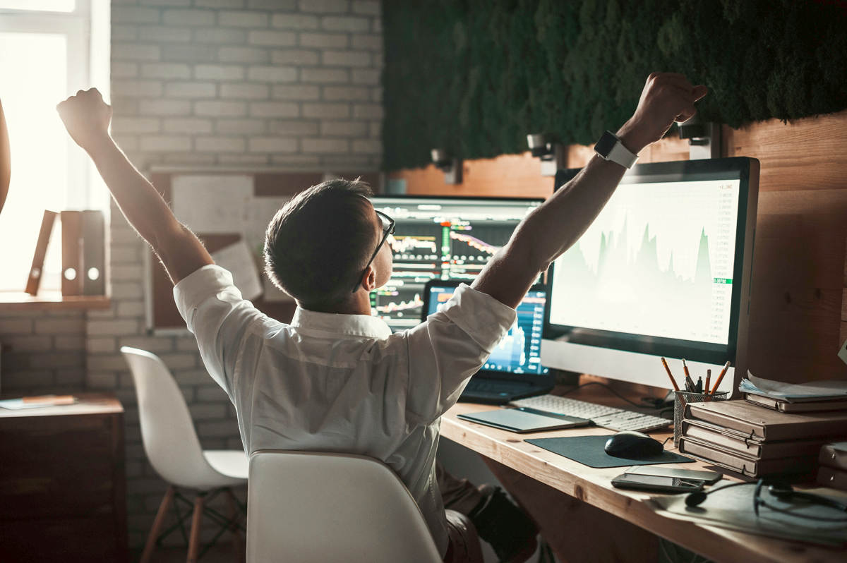 Young man in casual wear gesturing while sitting at the desk in creative office | Investing 101: A Beginner's Guide To Investing | investing for dummies