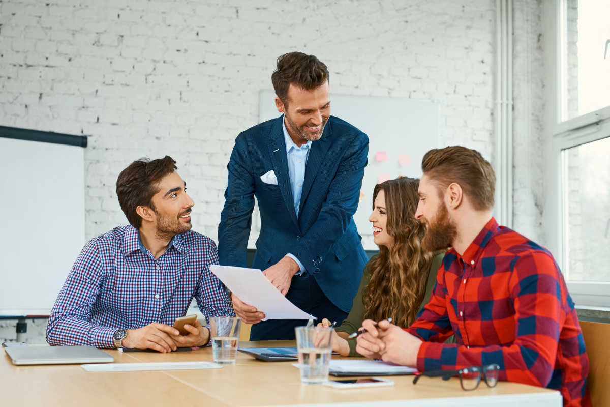 Team leader talking with coworkers in modern office | How to Be More Social and Outgoing | situations