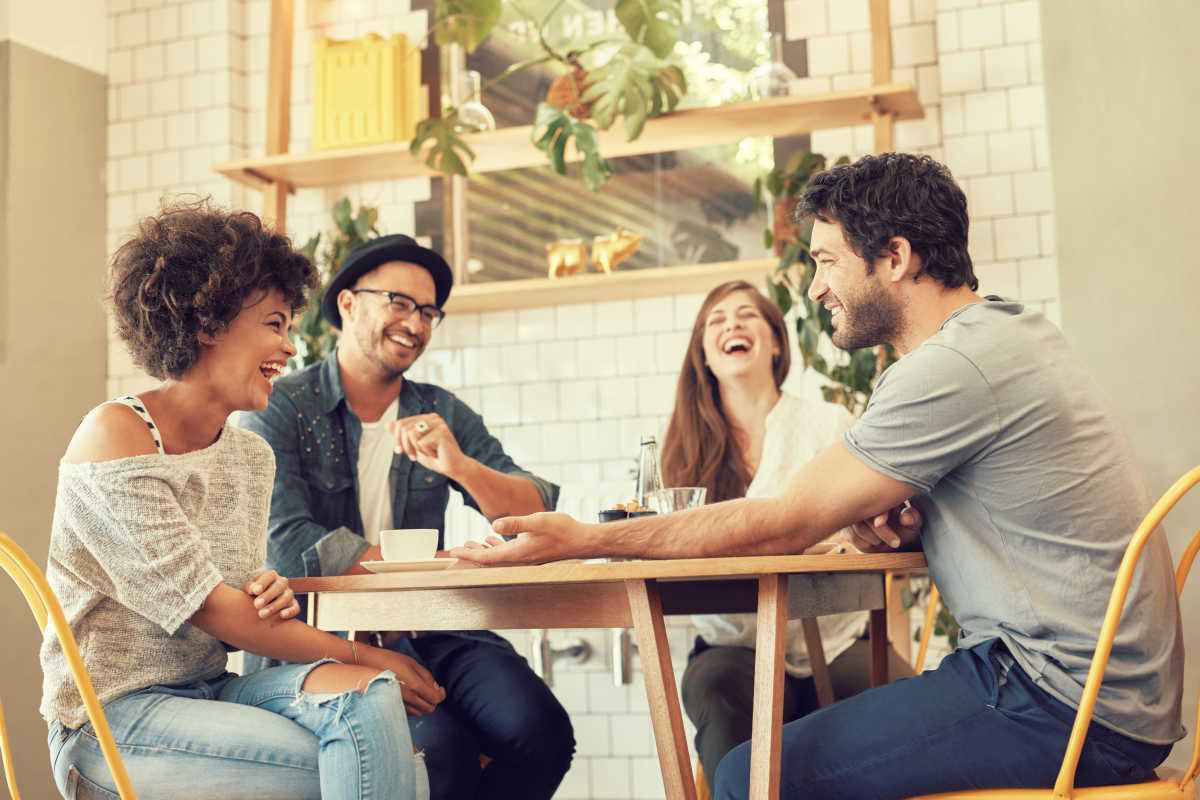 Group of young people sitting in a coffee shop and smiling | How to Be More Social and Outgoing | how to be more social in college