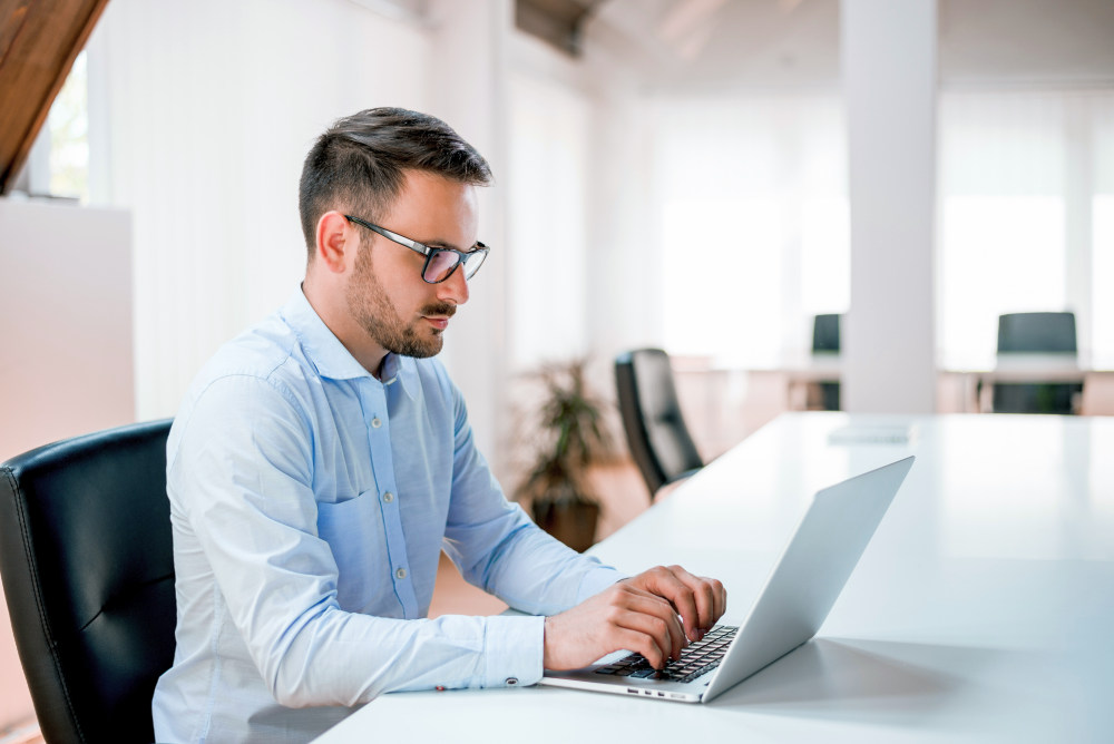 Businessman sitting at office desk working on laptop computer   How To Write a Two Weeks Notice Letter And Quit On Your Own Terms   two weeks notice template