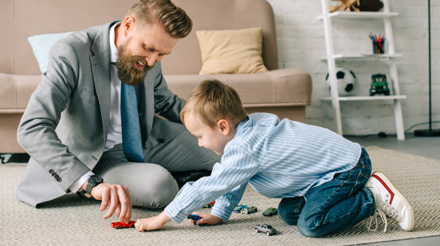 Businessman in suit and little son playing with toy cars on floor at home | How to Become a Cool Working Dad | what makes a good dad | Featured