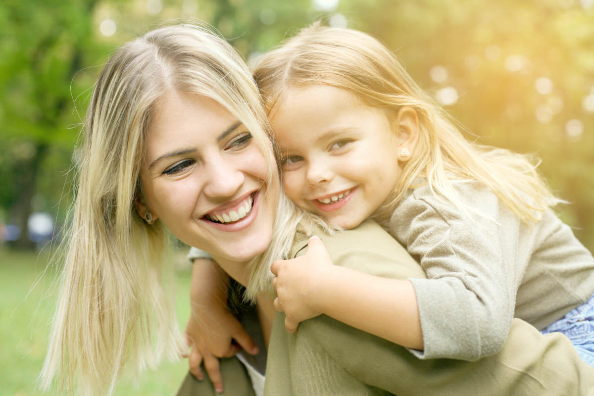 Cute young daughter on a piggy back ride with her mother   Working Moms Tips: Balancing Work and Family   how to balance work and family