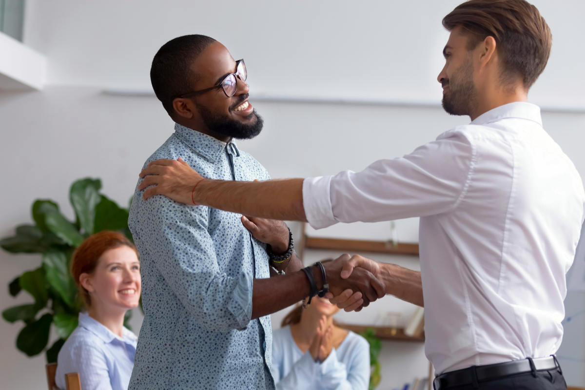 Diverse people gathered in meeting executive manager shake hands with black employee | Steps To Stop Complaining And Be Happier | how to tell someone to stop complaining
