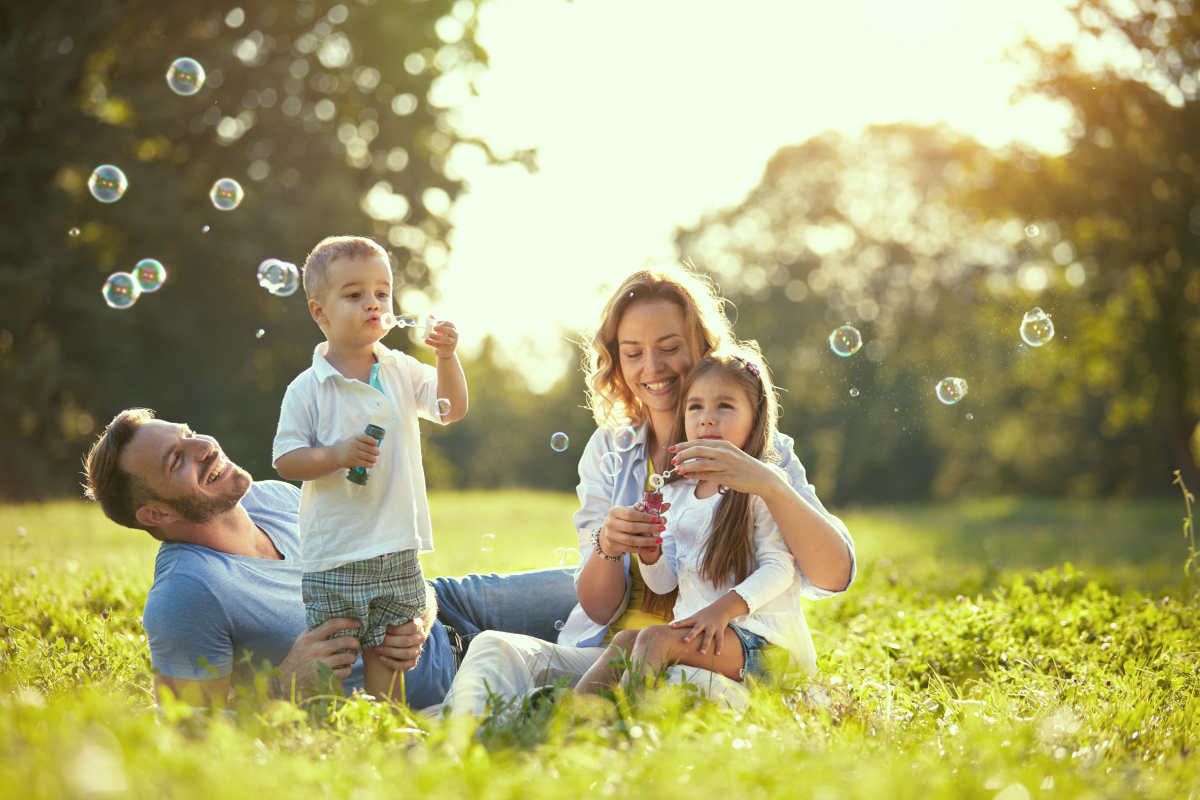 Family with children blow soap bubbles outdoor | Life Skills To Master Before 40 | basic life skills