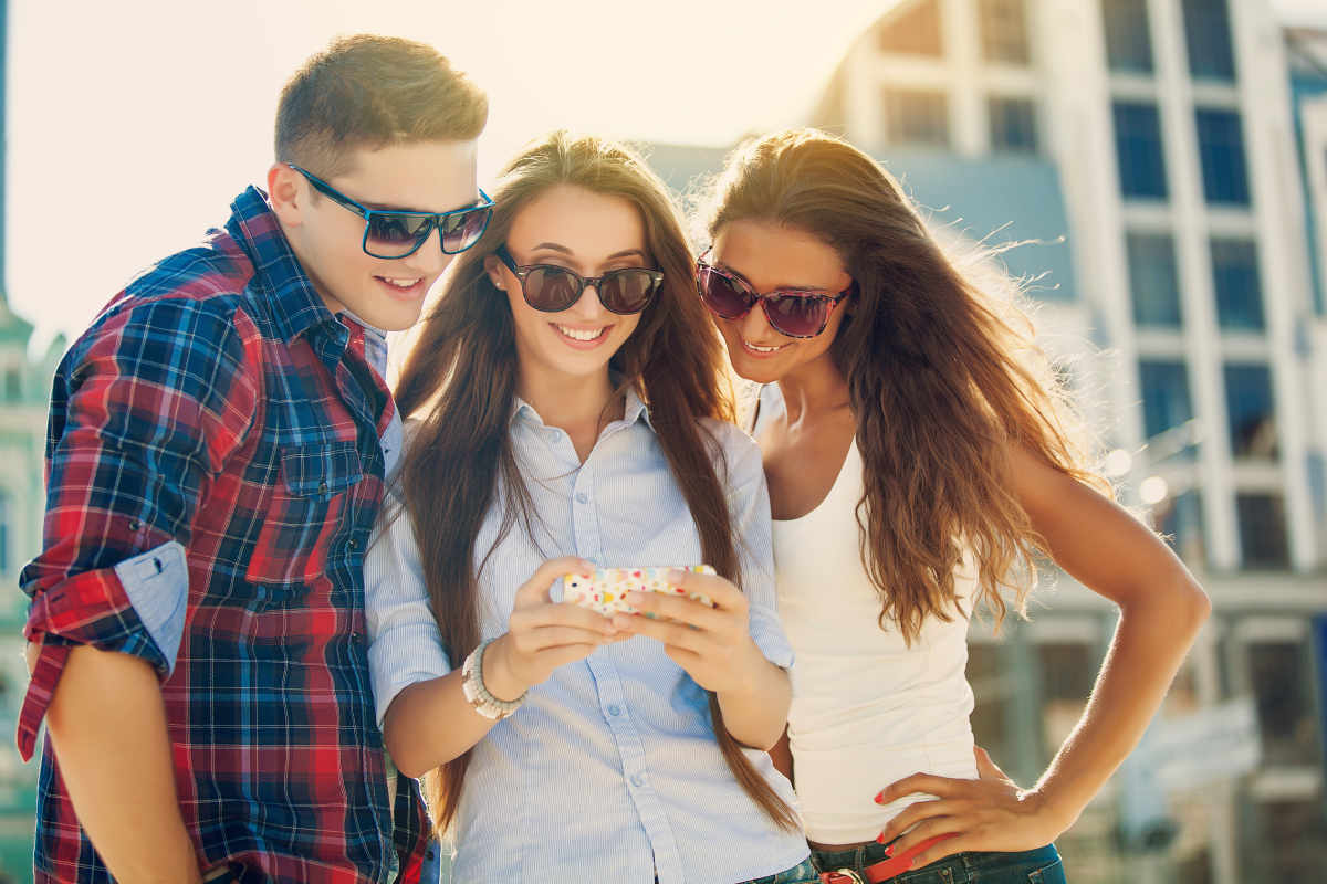 Friends amazed watching the smart phone outdoor | Social Media Etiquette Tips For Smart & Responsible Social Networking | social media and relationships
