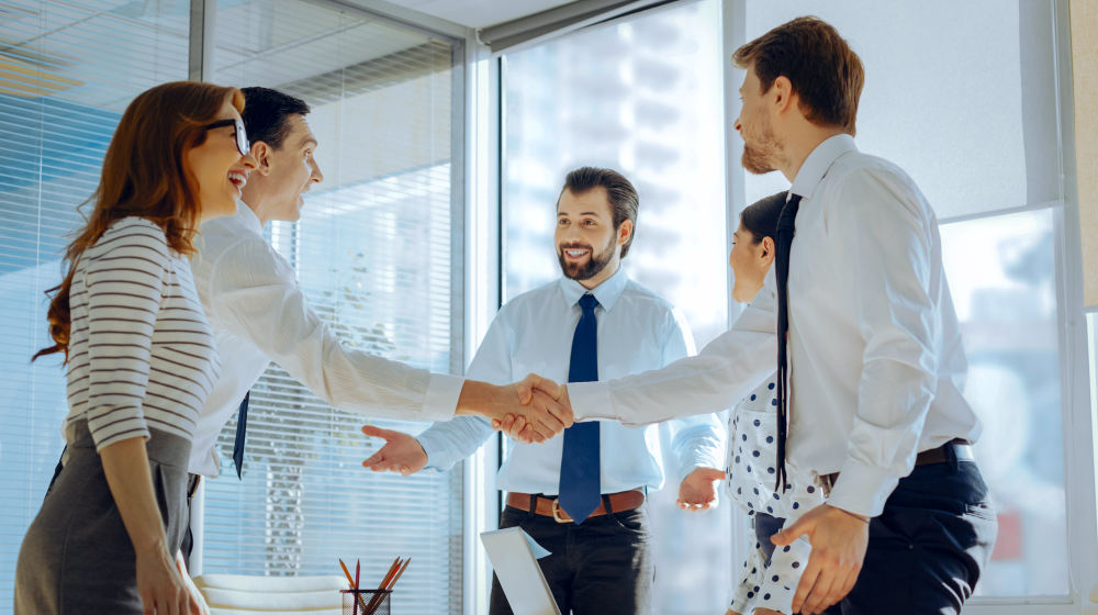 Upbeat young employees smiling brightly and shaking each others hands while congratulating each other | Reasons Why You Should Think Big | Think Big and Kick Ass | Featured