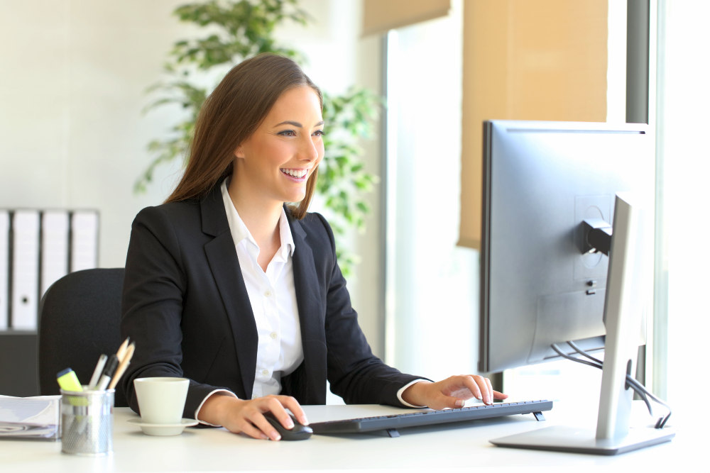 Happy executive working with a desktop computer at office   How To Write a Two Weeks Notice Letter And Quit On Your Own Terms   resignation letter