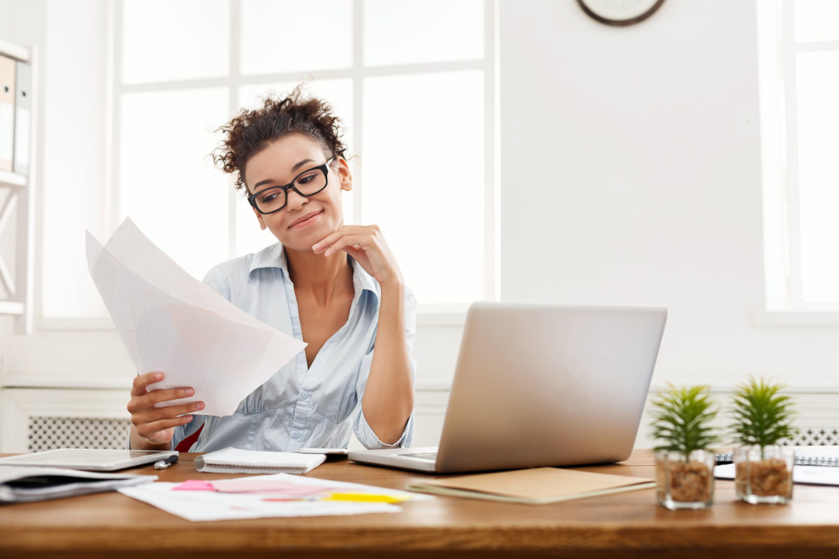 Smiling business woman in formal wear sitting at wooden desk in modern office | Steps To Stop Complaining And Be Happier | why do people complain