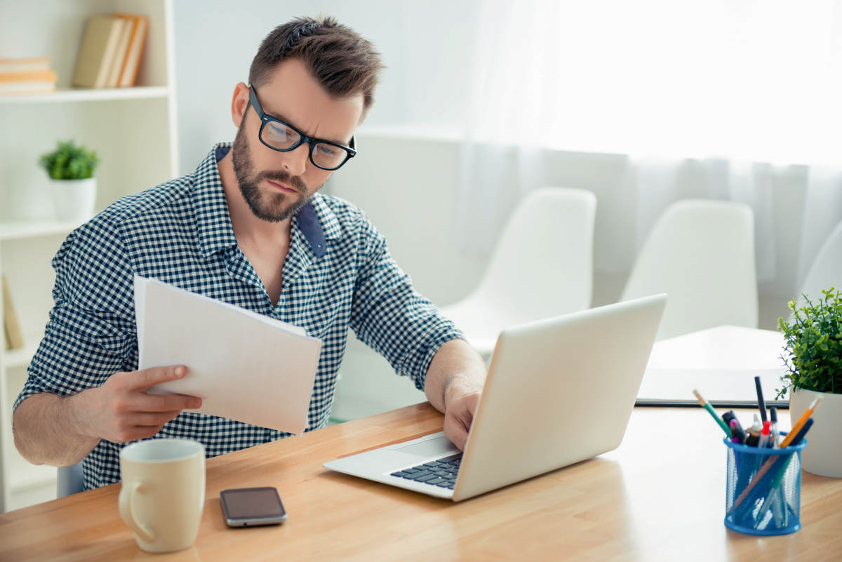 Concentrated businessman in glasses with laptop reading | Self-Improvement Goals For Entrepreneurs And How To Achieve Them | self improvement ideas