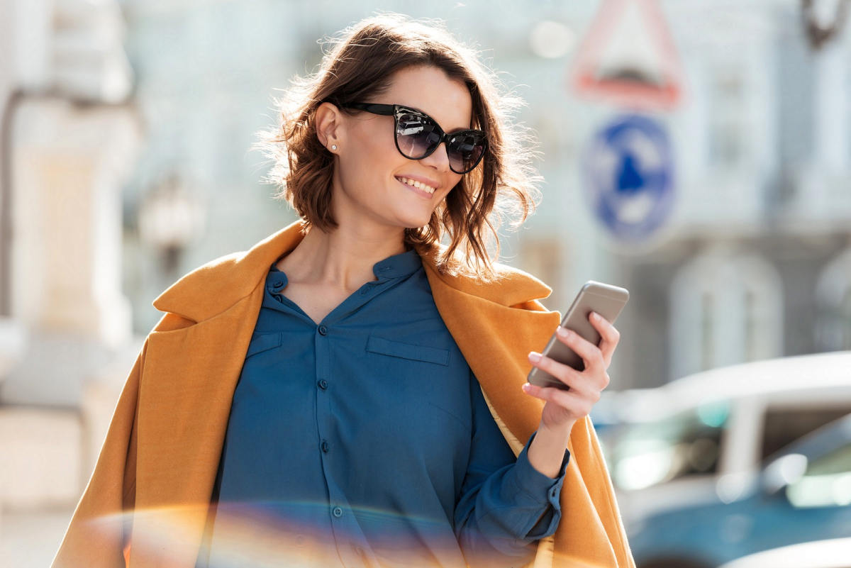 Smiling casual woman in sunglasses looking at mobile phone while standing on a city street | Social Media Etiquette Tips For Smart & Responsible Social Networking | social media pros and cons