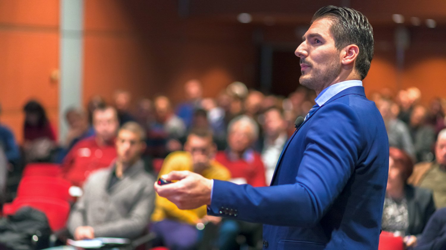 Speaker giving a talk on corporate Business Conference   The Best Ted Talks Of All Time   what are the best ted talks reddit   Featured