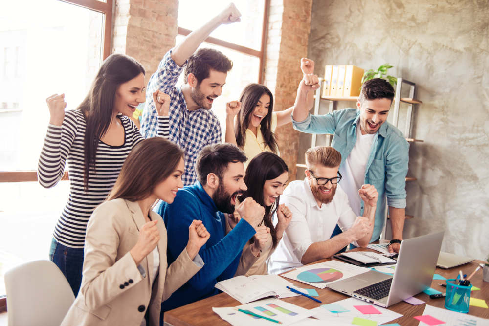 Group of business partners with raised up hands in light modern workstation, celebrating the breakthrough | Top Business Advice From Successful Business Owners | successful business