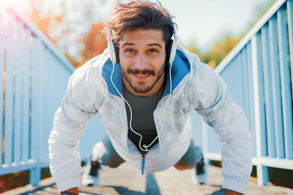 Young sportsman listening to music while doing push ups outdoors | Tips to Sleep Soundly for Better Productivity | how to get a better night sleep