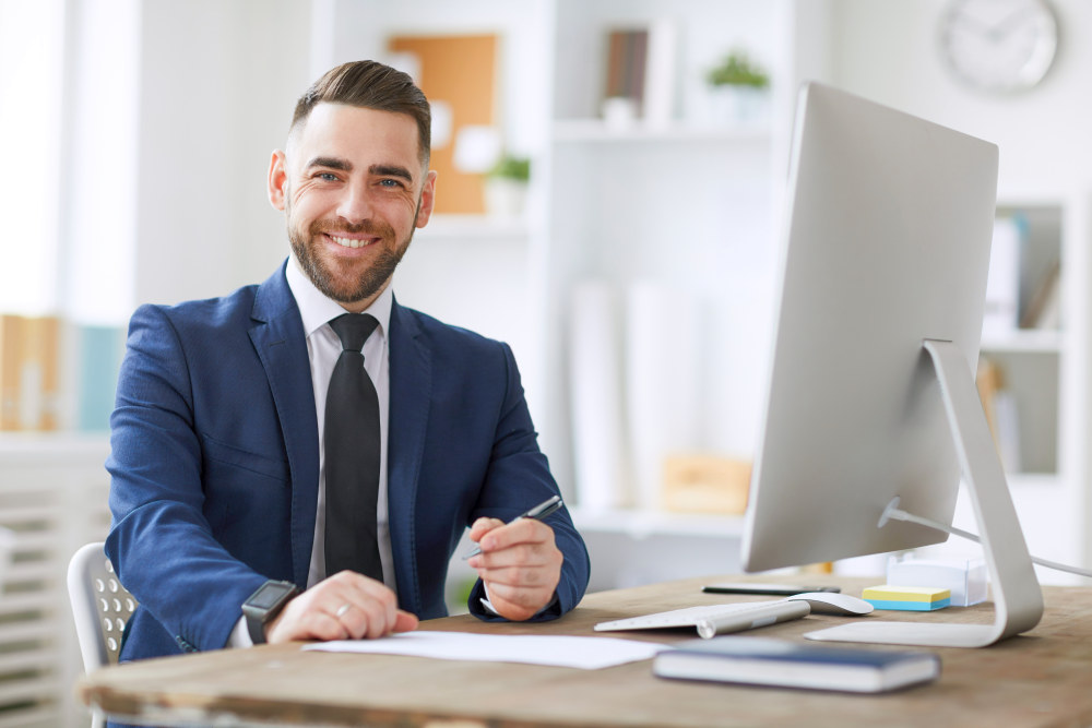 Young successful businessman in formal wear looking at you with smile while sitting by workplace in office | Reasons Why You Should Think Big | The Big Think