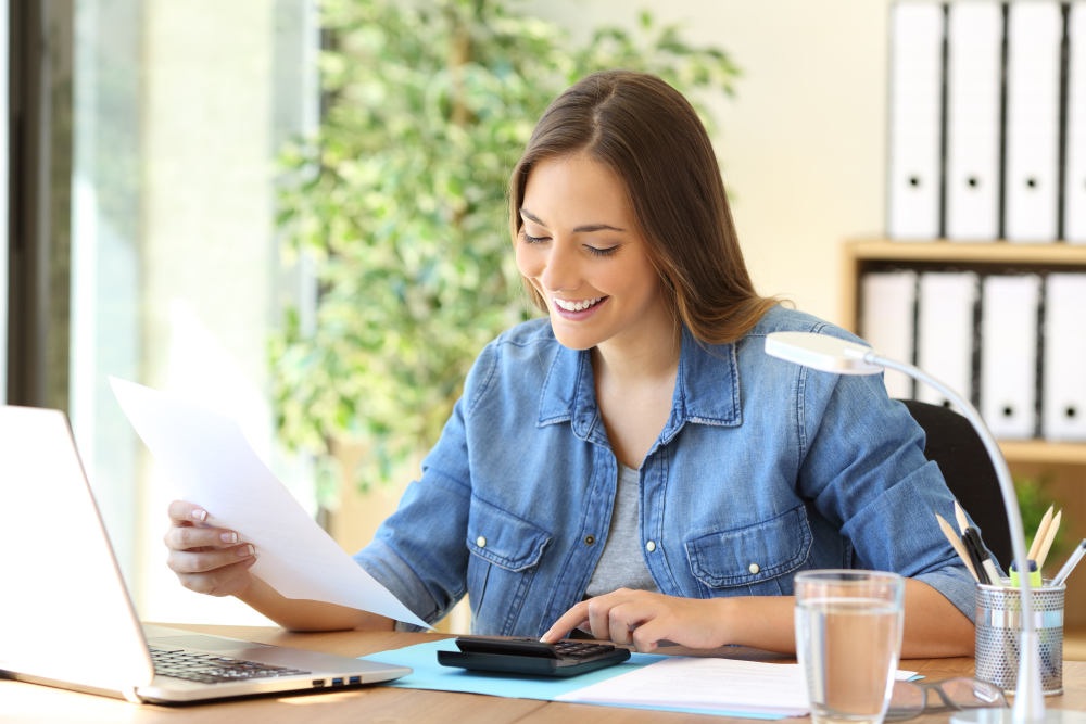 Freelance woman calculating a budget in a desktop at office | How To Manage Your Holiday Finances | holiday finance | holiday budget