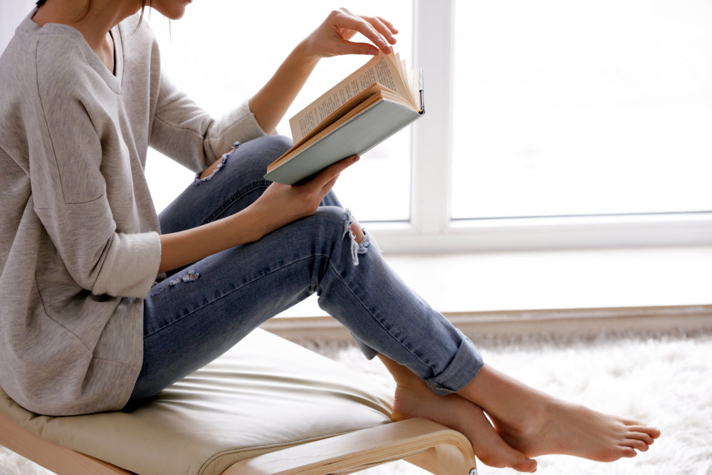 Beautiful young woman reading book near window at home | Powerful Quotes By The Nation's Most Powerful People | short powerful quotes
