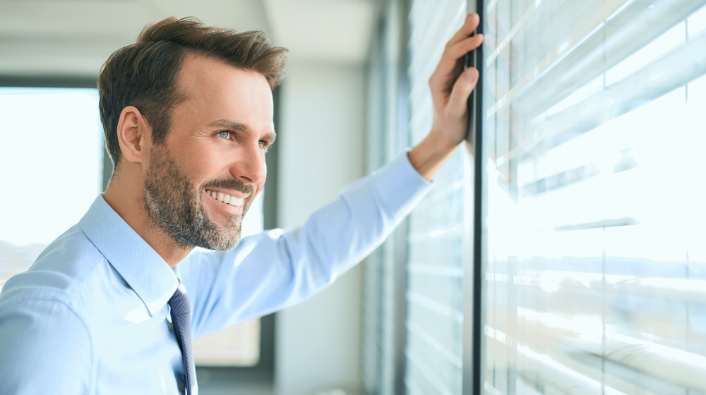 Businessman looking though the window at modern office | Joy Vs. Happiness: How To Achieve Both | joy vs happiness | joy vs happiness quotes | Featured