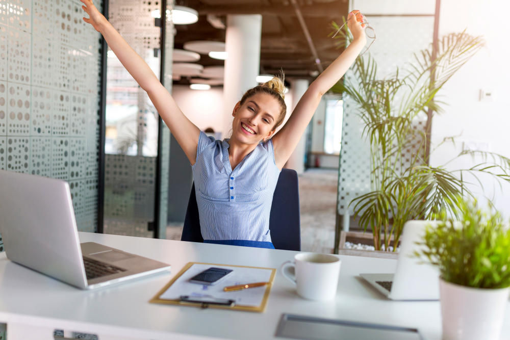 Businesswoman With Laptop Celebrating Success At Office Desk | Positivity Quotes By Top Entrepreneurs