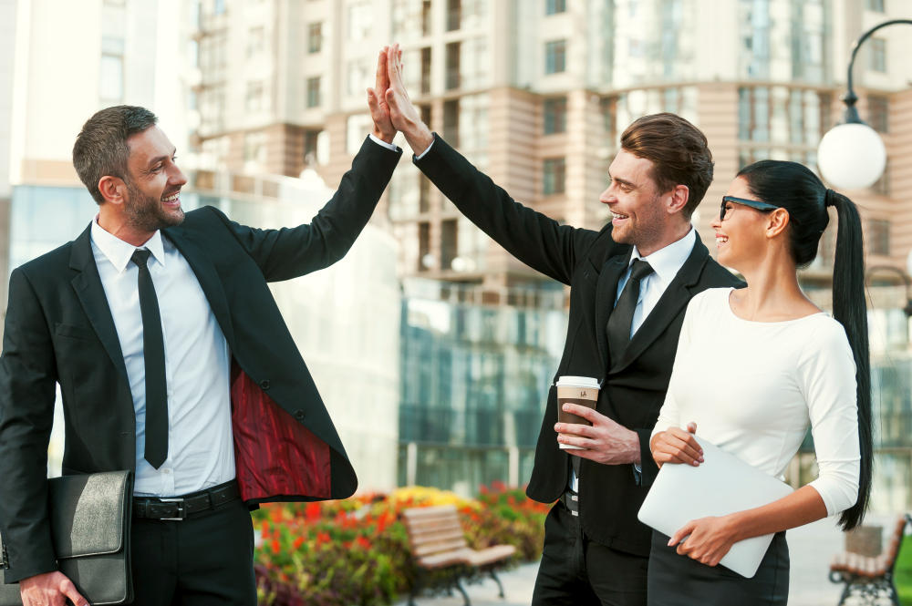 Two happy young businessmen giving high five | Positivity Quotes By Top Entrepreneurs