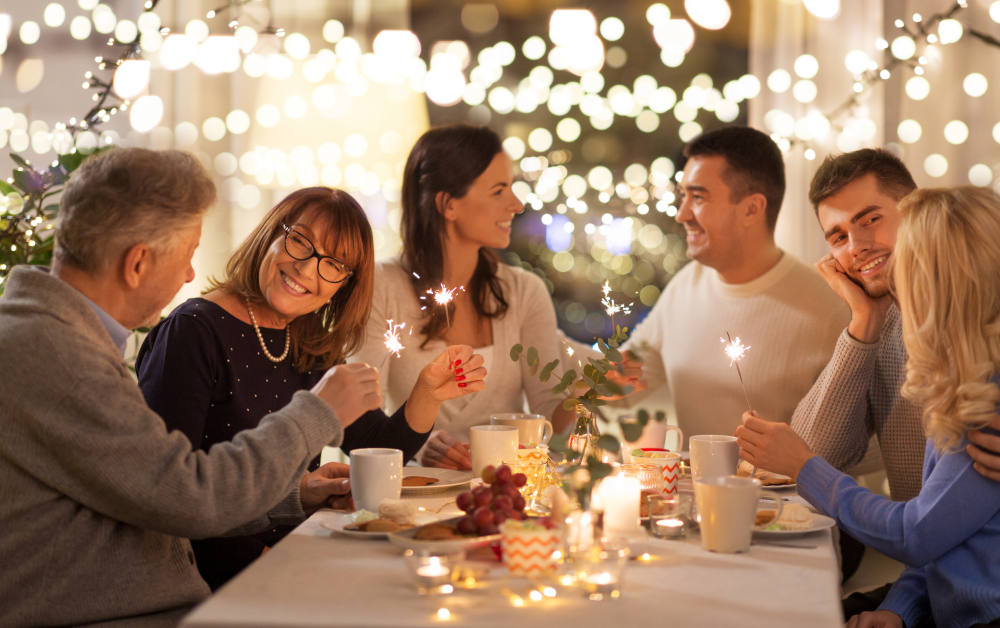 Happy family with sparklers having fun at dinner party at home | Sources of Holiday Stress And How To Beat Them | holiday stress reliever