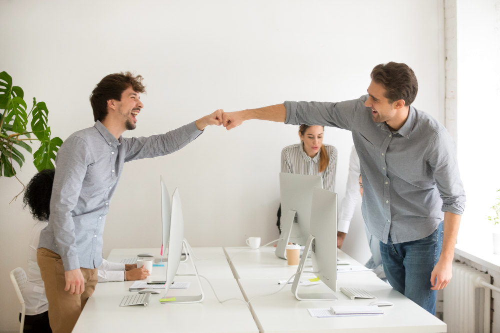 Cheerful male colleagues fist bumping celebrating successful teamwork in office | Powerful Quotes By The Nation's Most Powerful People | motivational quotes