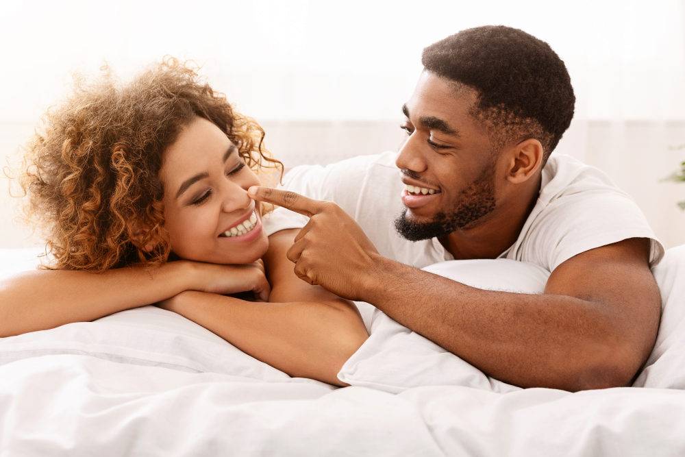 Playful african man flirting with wife, touching her nose in bed | How To Be Better In Bed For Romantic Love-Making | Romantic Love Making | romantic things to say while making love
